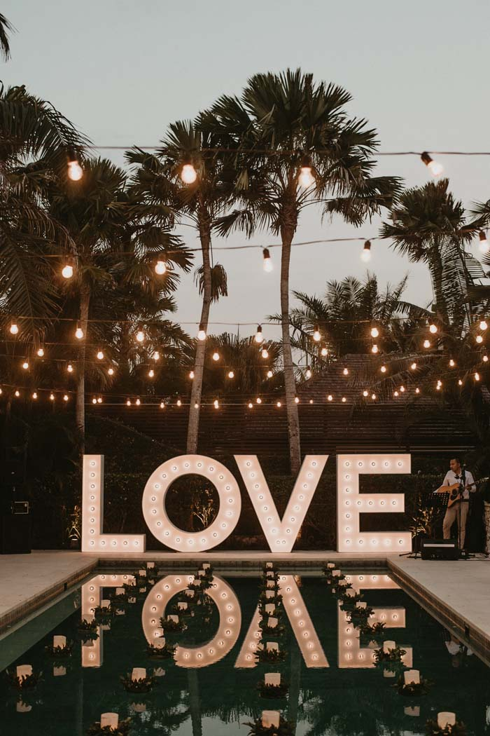 wedding by the pool and lit up LOVE sign