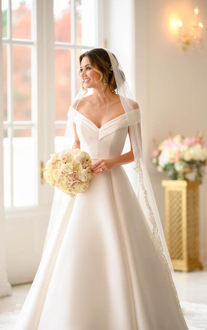 bride wearing off the shoulder wedding dress and veil