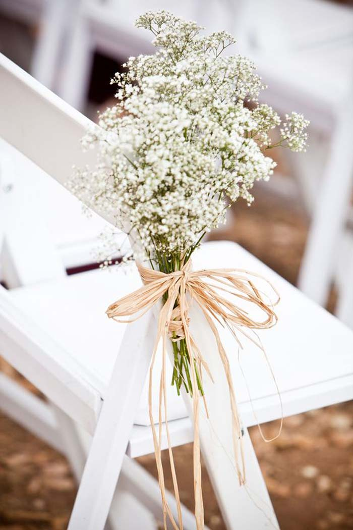 flowers on chairs to style wedding aisle